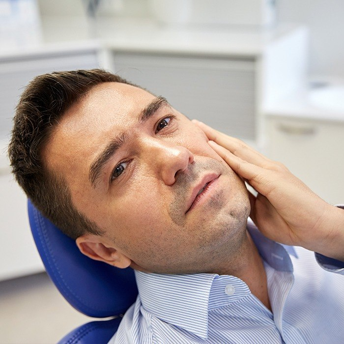 Man holding cheek in dental chair