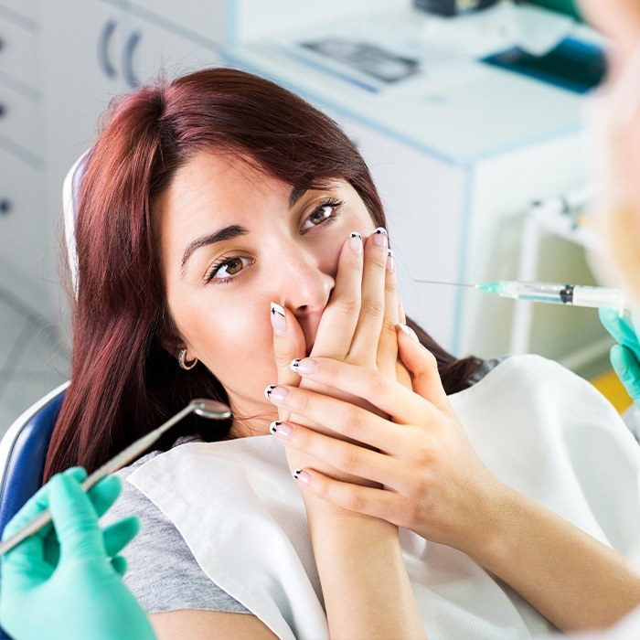 Woman in dental chair covering her mouth