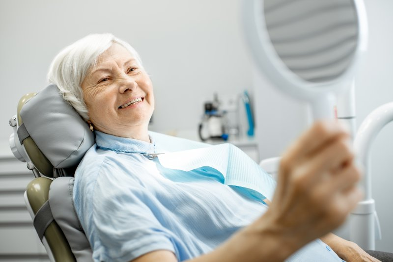 Elderly patient smiling in mirror at appointment
