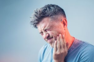man in pain who needs emergency dentist in Lexington