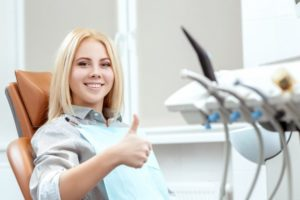 Woman in dental chair with blonde hair smiling with thumb up