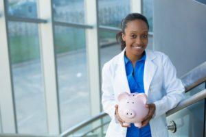 smiling dentist holding a pink piggy bank